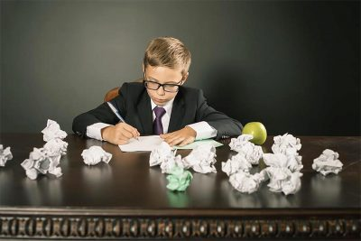 boy writing on table