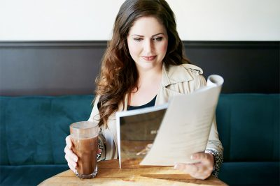 woman reading paper with drink